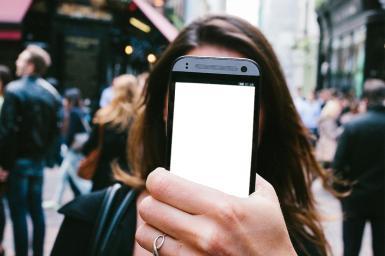 Приколы. Рамка, фотоэффект: Прикол с селфи. Фотомонтаж, коллаж. Селфи на улице. Фотоприкол. Ваше лицо на экране смартфона. Большой город на заднем плане. Телефон в руке.